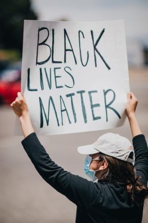 Woman holding sign reading black lives matter
